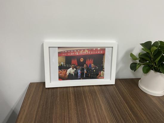 """代孕公司""""优孕行""""广州分公司总经理蔡德亮自称为人大代表,其在办公室所展示的参加江西上饶市广丰区第十六届人大四次会议合照。"""